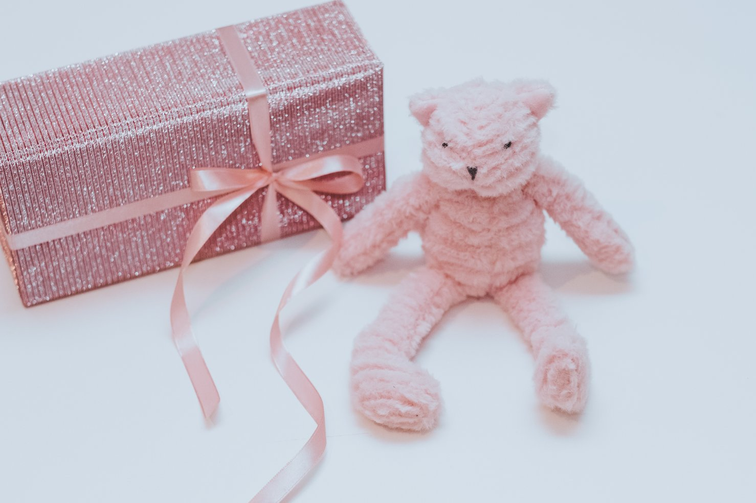 An image showing a teddy bear and a box in gift wrapping. Offering product discounts and free gift wrapping should be part of your Mother's Day marketing campaign.