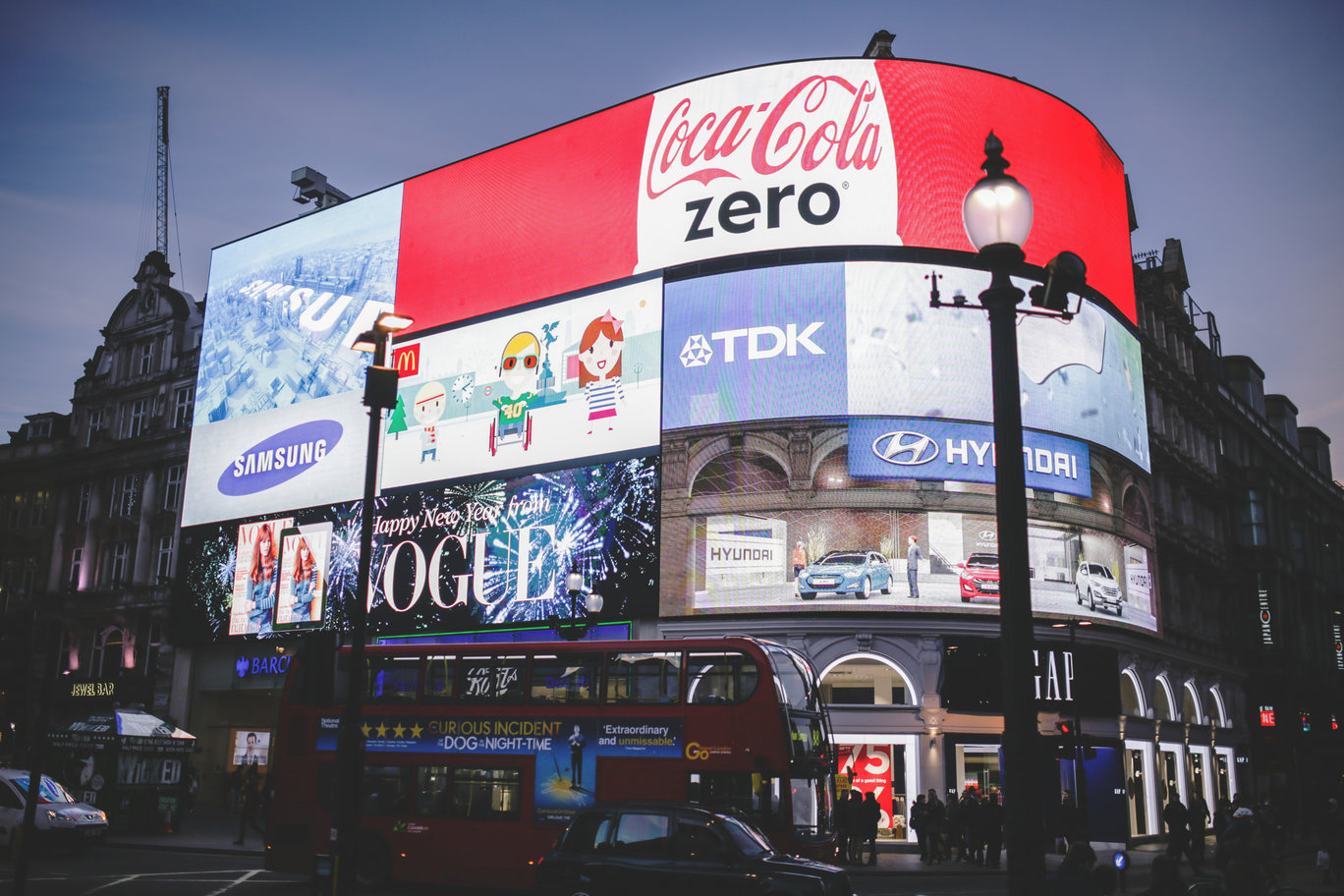 Image showing brightly-lit billboard with lots of marketing adverts, highlighting the fact that this kind of marketing may be a thing of the past, replaced with e-commerce personalisation instead.