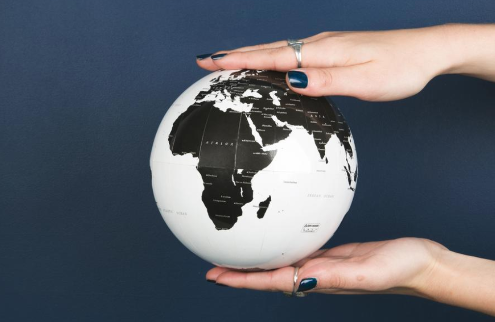 Person holds a globe between their hands against dark blue backdrop