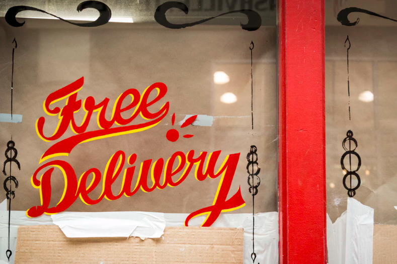 "Hand lettering signage reading ""free delivery"" on a glass window"