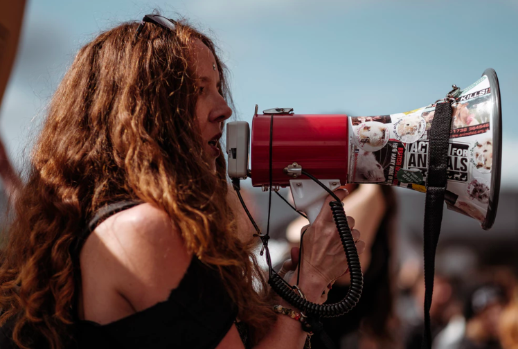 women at a protest with a microphone