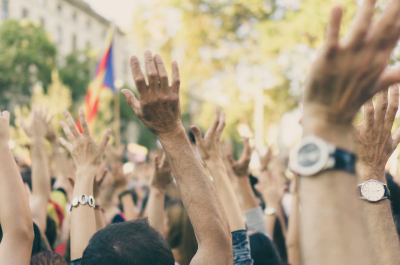 crowd of people with hands raised