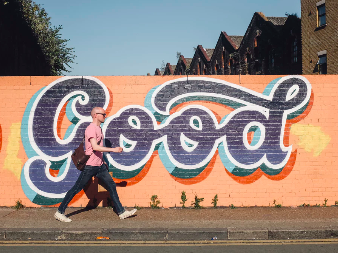 man walking past the word good painted on a wall