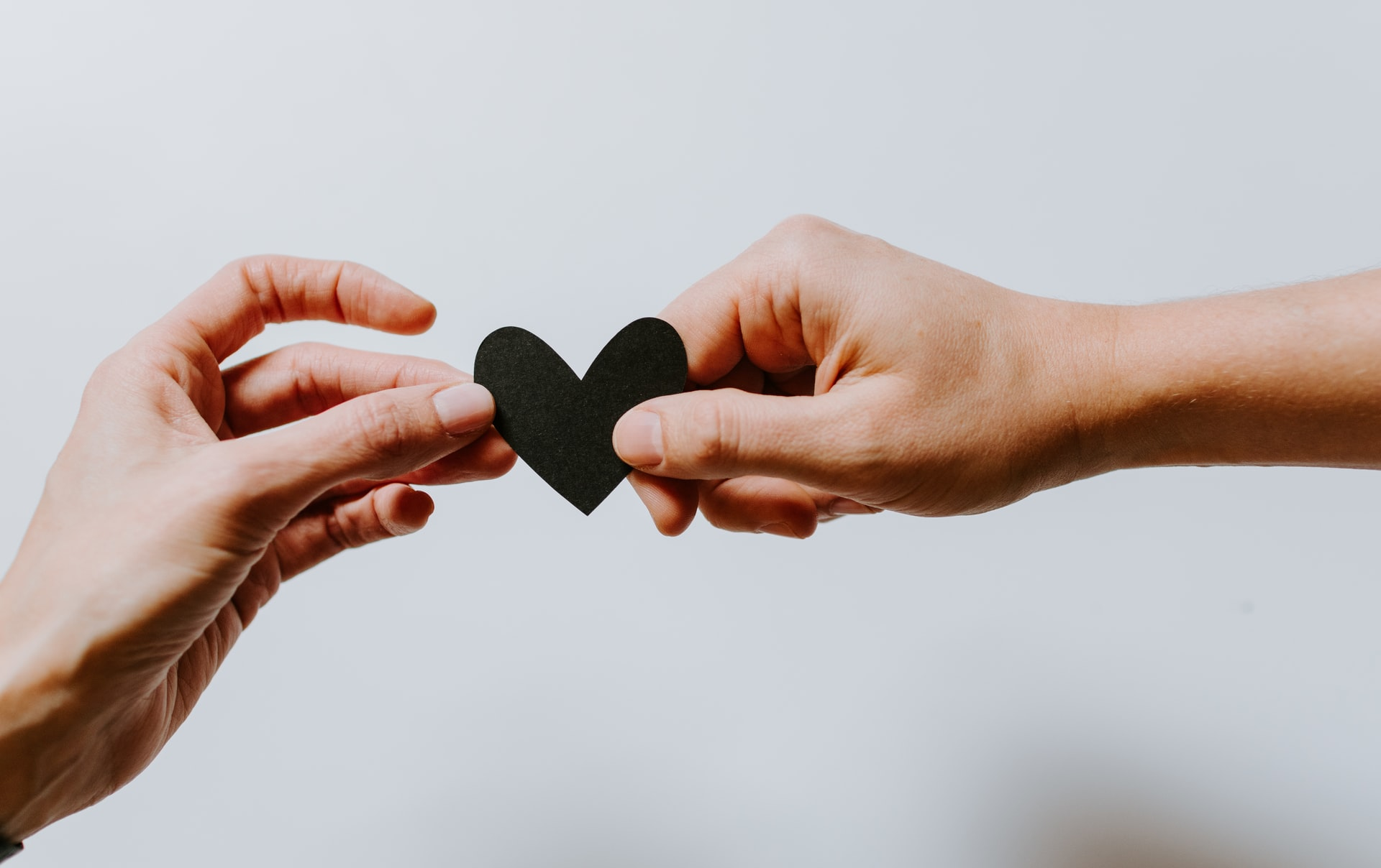 Two hands exchanging a heart
